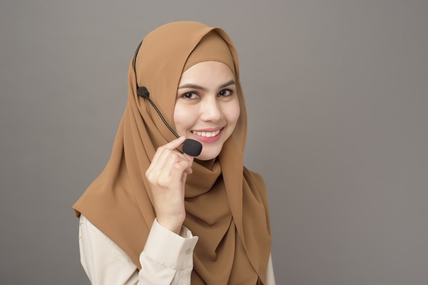 portrait of beautiful call center woman with hijab on gray background